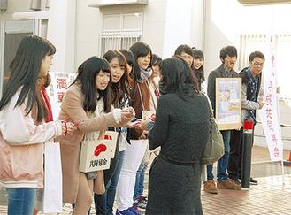 道行く人に元気に声をかける学生たち