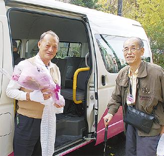 初の運行日、運転手に花束を贈呈する清水会長(右)