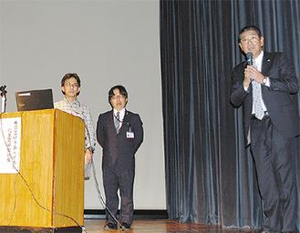 日立ゆうあんどあいで働く社員(左の2人)を紹介する鈴木巌氏