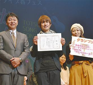 賞状を手にする伊与木さん。左は石井運営委員会委員長