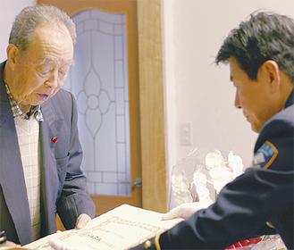 坂本署長から勲記を受け取る金子さん(写真左)