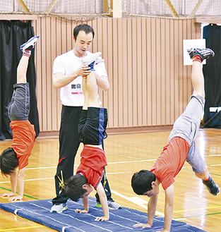 元体操選手の鹿島さんに逆立ちを教わる子どもたち
