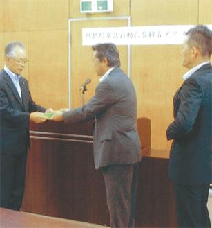 録音機を常盤会長(左)に手渡す飯島支部長