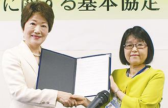 締結書を示す、都築理事長(左)と田雑区長