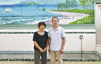 壁画を背景に微笑む江尻夫妻