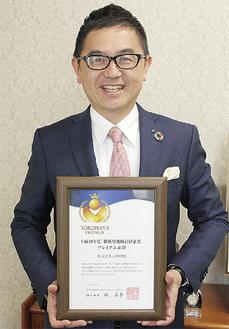 表彰状を持つ大川社長
