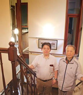 しゃれた吹き抜けの階段。石黒世話人代表(左)と小松さん