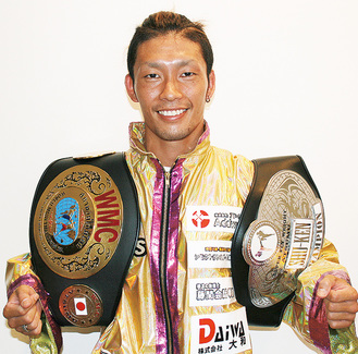 2つのチャンピオンベルトを肩にかける理崎さん