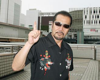 戸塚駅をバックにポーズを決める翔さん