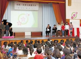スクリーンに映された校章と、紹介する児童