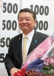 当確後、花束を受け取る松田氏