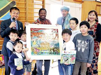 作品を持つヤフィドゥさん(上段左から2番目)と児童ら