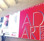 世界貿易センターに展示された作品を前にする坂本さん(上)「今後も芸術作品、記念写真両方を大切にする」と話す(左下)。