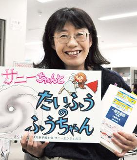 気象学の専門書と講座で使う自作の紙芝居を持つ遠藤さん