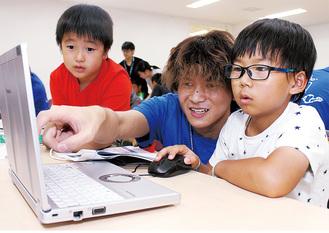 学生の指導のもと真剣な表情でパソコンを操作する児童