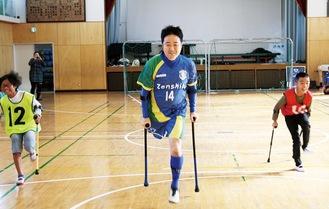 クラッチという杖を持って遠藤さん(中央)と競争する児童。チームに分かれゲームも楽しんだ(右下)
