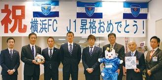 祝賀の横断幕の前に立つ(左から)上尾社長、吉泉区長、武田選手、南選手、下平監督と区役所職員