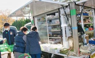 移動販売車に並ぶ商品を買う平戸高層団地の住民