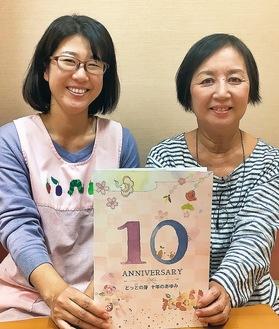 昨年末発行の10周年記念誌を持つ福本さん(左)と高村さん