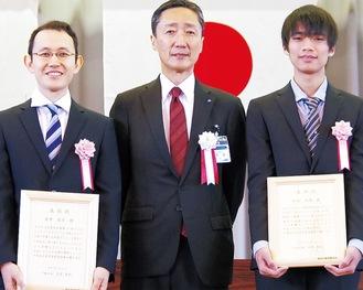 賞状を手にする倉井さん(左)と松本さん。中央は吉泉区長