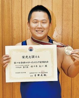 メダルと賞状を手にする佐々木さん