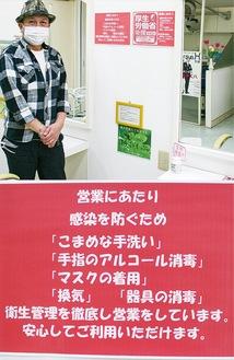 佐藤さんと店内に掲示される安全性を訴える掲示物