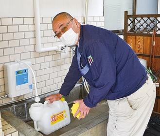 ポリタンクへ次亜塩素酸水を入れる伴会長