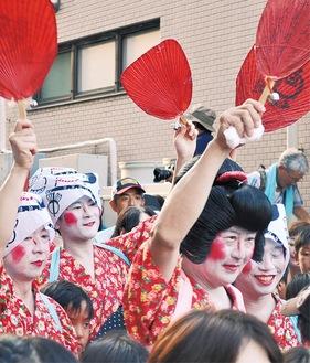 「お札まき」では例年女装した男たちが踊りを披露