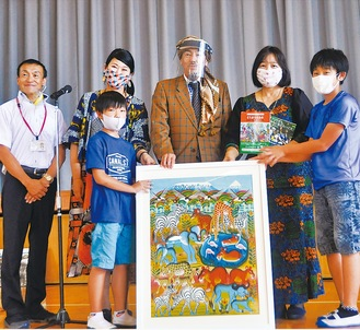 島岡強さん(中央)などから作品を受け取る児童