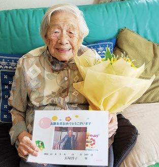誕生日プレゼントを手に笑顔を見せる長塚さん