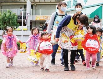 お菓子袋を持って歩く園児