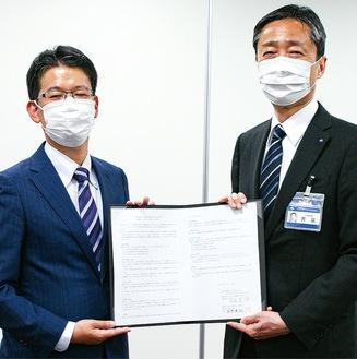 協定書を手にする吉泉区長(右)とジェイコム代表者
