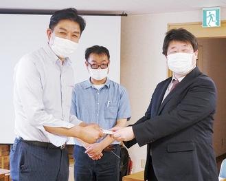 目録を受け取る高橋勇美専務理事(右)