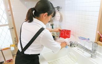 食事の後の片付けをするスタッフ。清潔感のあるキッチンに