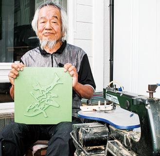 作品を手にする久野さん。電動卓上糸鋸盤と。