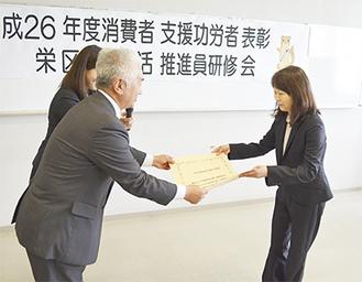 尾仲区長から賞状を受け取る小橋会長(右)