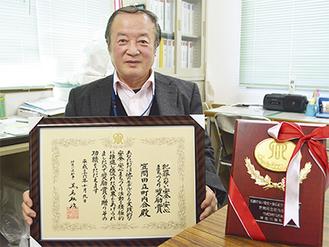 賞状を手にする岡田会長と記念品の盾