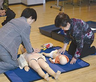 小児や乳幼児の人形で胸骨圧迫をする参加者
