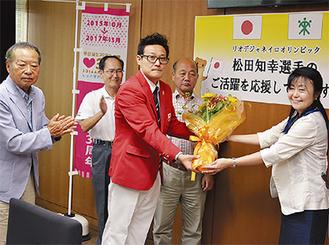 小山内区長(右)から花束を受け取る松田選手(中央)