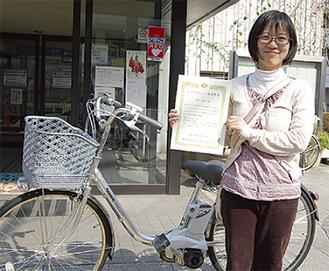 最優秀賞の下村さんと賞品の電動自転車