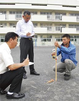 校庭の線量を測定する職員ら