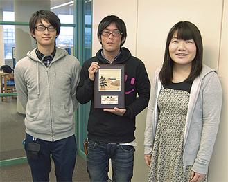 優勝盾に笑顔のメンバー(左から西村さん、藤倉ゼミ長、柴山さん)