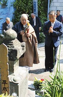 山本住職による読経の中、墓に手を合わせる小川さん(右)