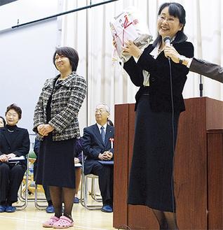 記念品を受け取り笑顔の服部校長(右)