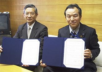 協定書を手にする林区長(右)と永村文庫長