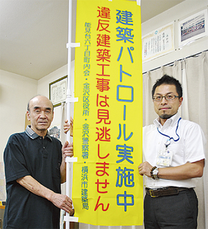 旗を受け取る千坂会長(左)