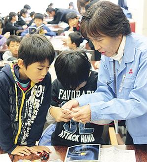 コイルの作り方を教わる児童