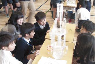 学生の指導でろ過実験をする児童