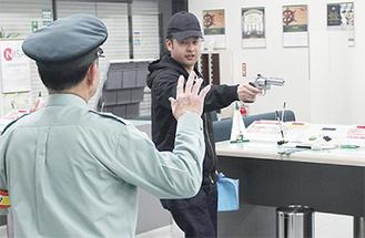 拳銃で脅す犯人役