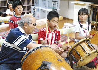 囃子の指導する平野さん(左)
